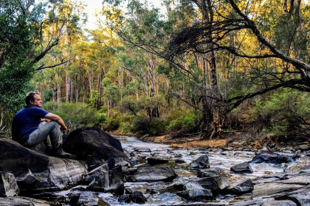 Man boosting his mental health by relaxing on a river on the Bibbulmun Track