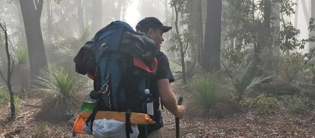 Man with large backpack in forest view on the Bibbulmun Track